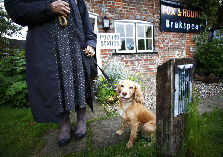 Image: A voter poses for a picture with a dog as they leave a pub being used as a polling station in Christmas Common, southern England