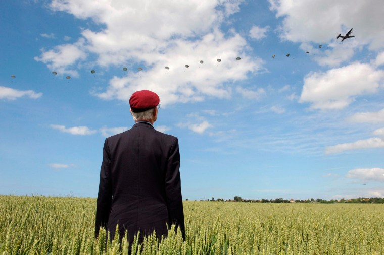 Image: British World War II veteran Frederick Glover poses for a photograph as soldiers parachute down during a D-Day commemoration paratroopers launch event in Ranville