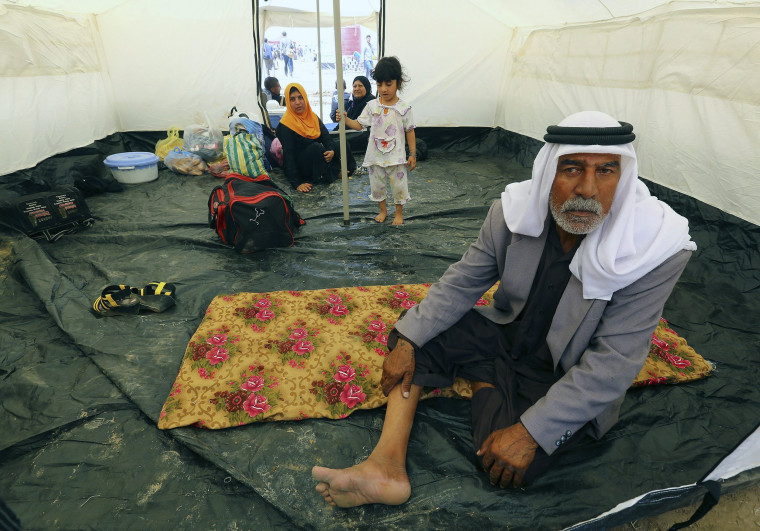 Image: A family, who fled from the violence in Mosul, sits inside a tent at a camp on the outskirts of Arbil