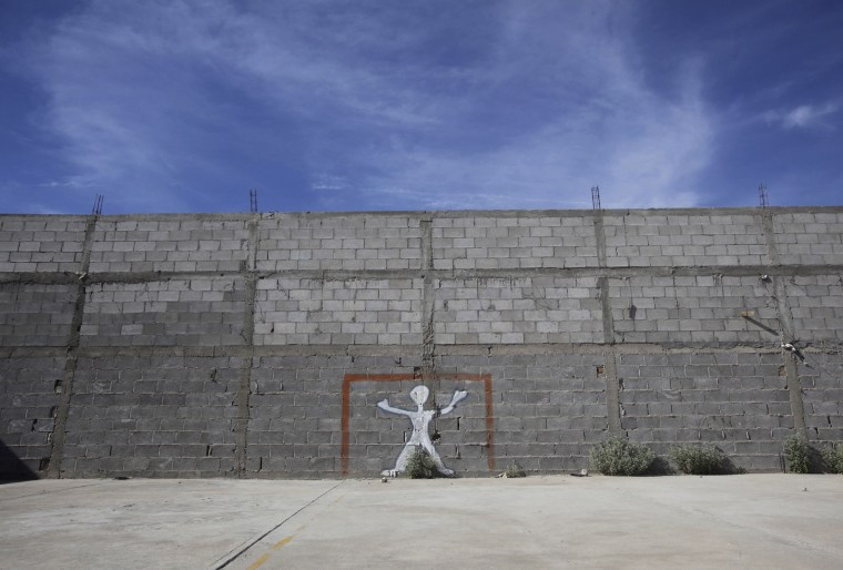 Image: A goalpost is painted on a wall at a house used as a creche in Ciudad Juarez