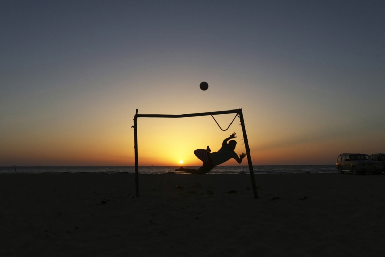 Image: A boy jumps to save a goal while playing soccer on the beach in Benghazi