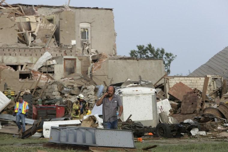 Image: A man talks on the phone in front of tornado-damaged buildings in Pilger, Nebraska