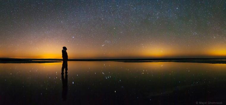 Image: The starry winter sky is merged into light domes of cities near Maranjab Salt Lake, Kashan, Iran