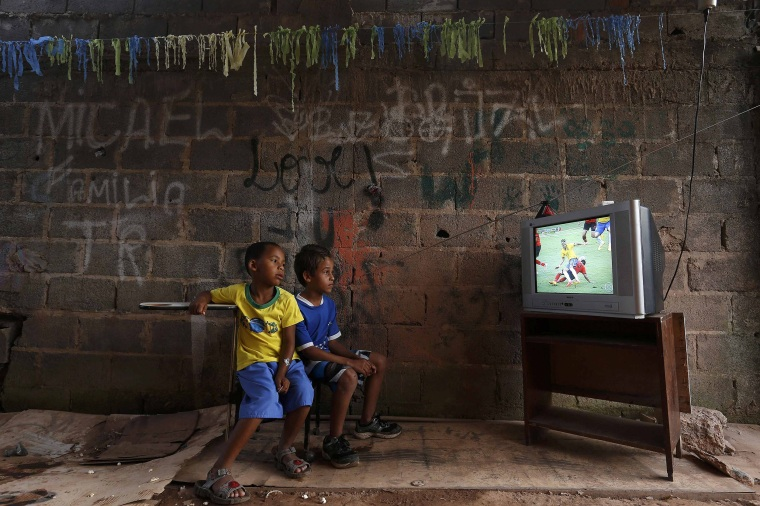 Image: Boys watch a screening of a 2014 World Cup soccer match on the outskirts of Brasilia