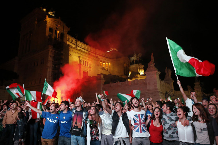 Image: People cheer as they watch the 2014 World Cup soccer match between Italy and England during a public viewing event in downtown Rome