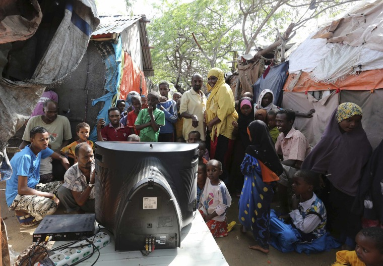 Image: Internally displaced Somali people crowd around a television set to watch the World Cup in Brazil highlights, in the capital Mogadishu