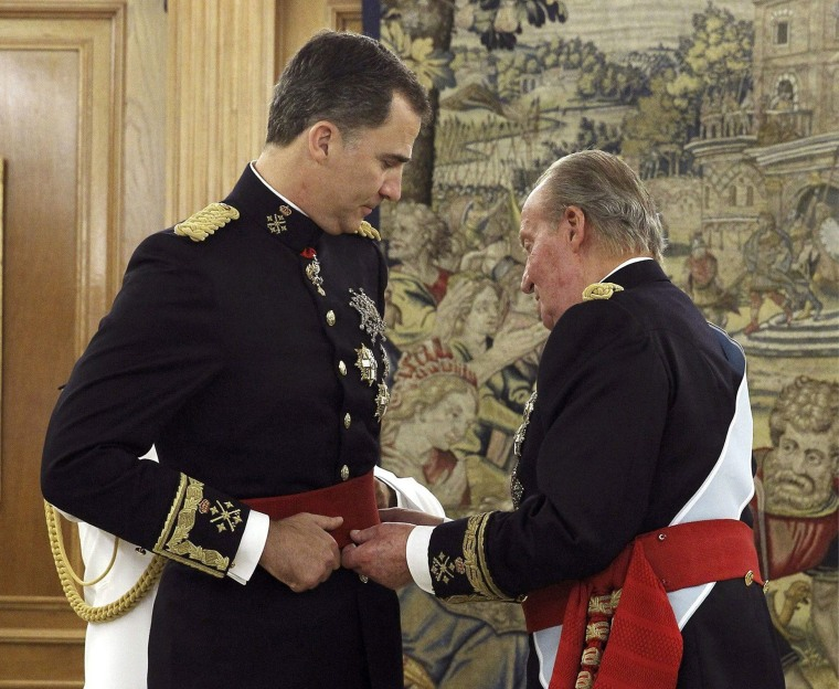 Image: Spain's King Juan Carlos places the Sash of Captain-General on new King Felipe VI during a ceremony at La Zarzuela Palace in Madrid