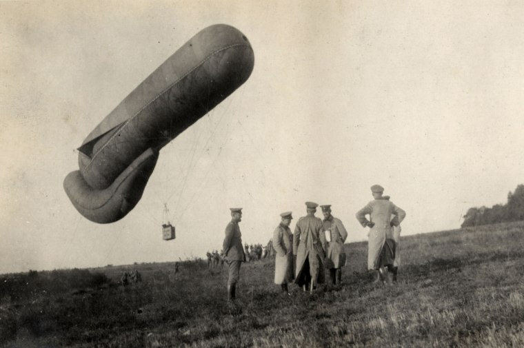 Image: German officers stand near an observation balloon near the Western Front in this handout picture taken in 1915