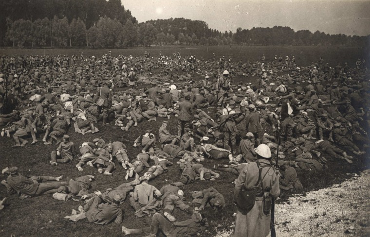 Image: Captured German prisoners lie down in a field at Longueau, on the Western Front, in this August 1, 1916 handout picture