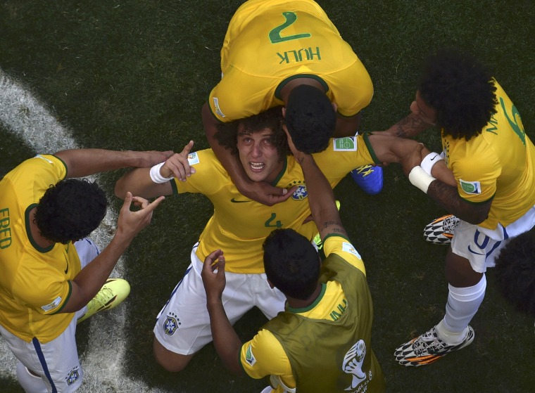 Image: Brazil's Neymar is assisted by his teammate Alves during their 2014 World Cup round of 16 game against Chile at the Mineirao stadium in Belo Horizonte