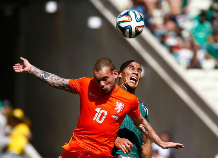Image: Wesley Sneijder of the Netherlands and Mexico's Carlos Salcido jump for the ball during their 2014 World Cup round of 16 game at the Castelao arena in Fortaleza