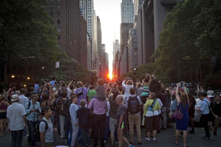 "Image: People take photos of the ""Manhattanhenge"" phenomenon in New York"