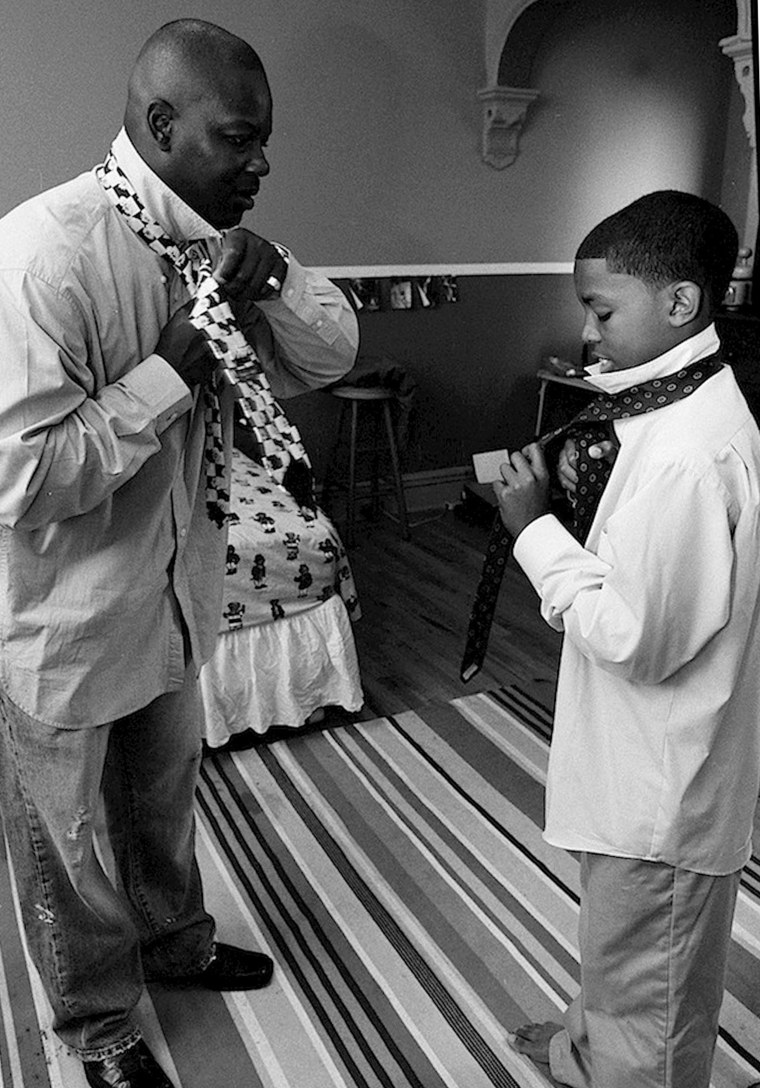 "Summer, 2005: The first time! Supreme teaches his stepson Tyshaun how to tie a tie for the first time. Supreme told me he loves being a stepdad. ""A stepfather is a man that steps up to be a dad."""