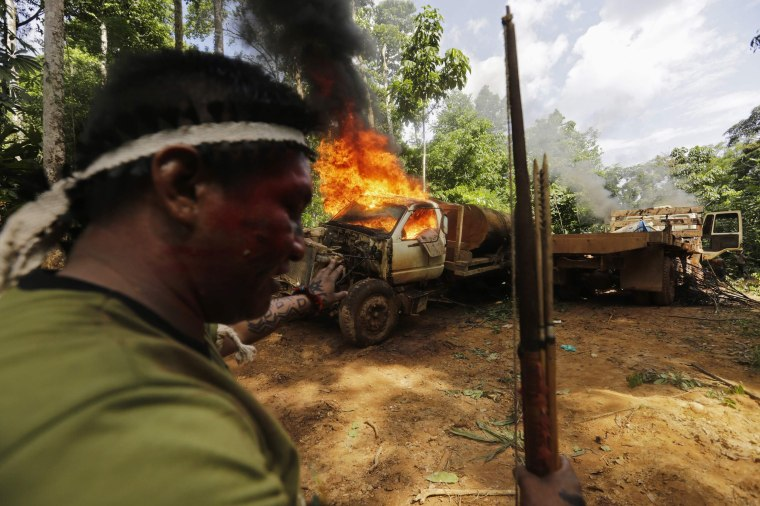 Image: A Ka'apor Indian warrior stands near logging truck they discovered and set on fire in the Alto Turiacu Indian territory