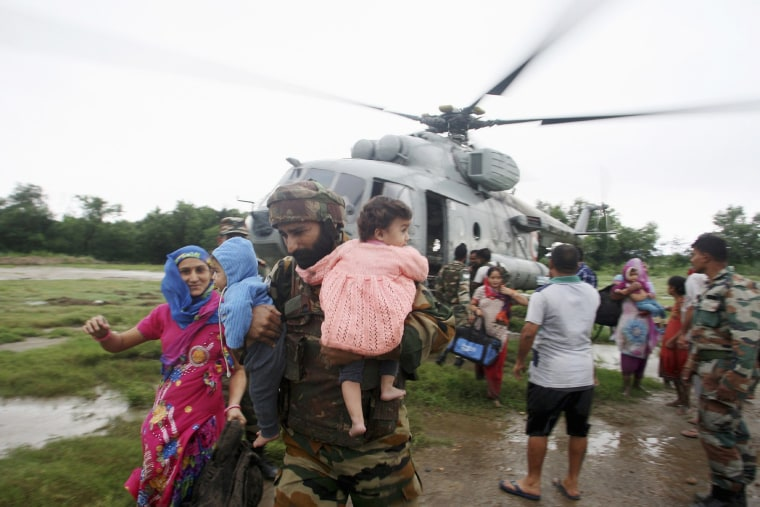 Image: An Indian army soldier carries two infants during rescue operation in Hamirpur Kona
