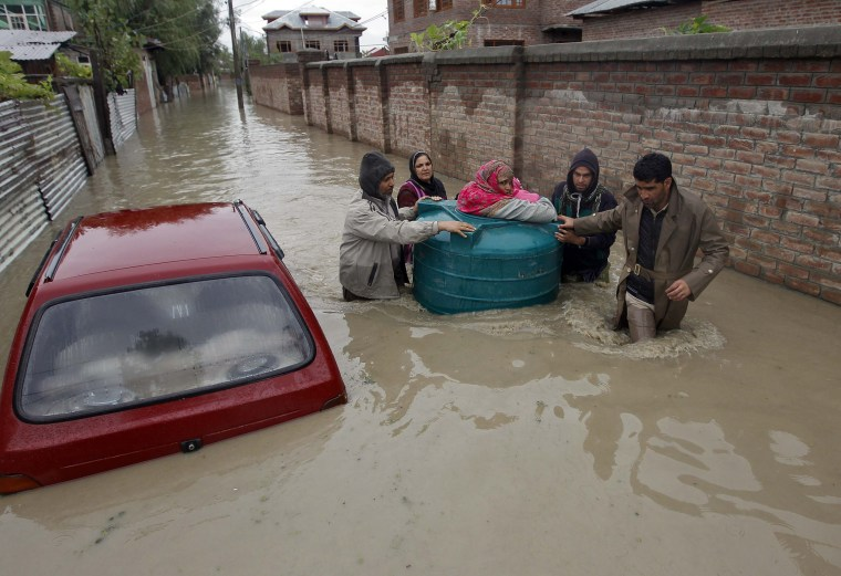 Image: People transport a sick woman in an empty water tank on a flooded street during rain in Srinagar