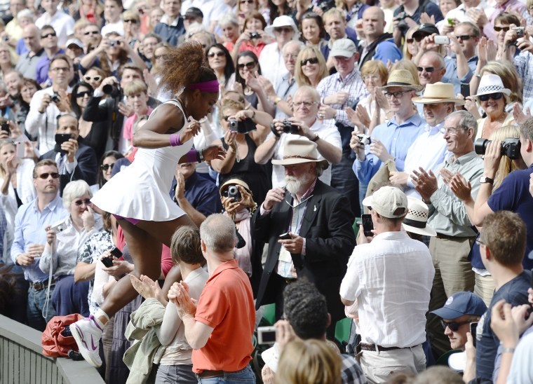 Serena Williams of the U.S. runs through the crowd to see her father and sister after defeating Agnieszka Radwanska of Poland in their women's final tennis match at the Wimbledon tennis championships in London
