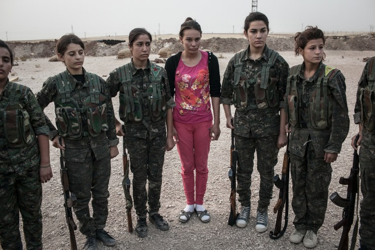 Dressed in pink, a young YPJ recruit arrives for her first day at a training base near Derek City, Syria.