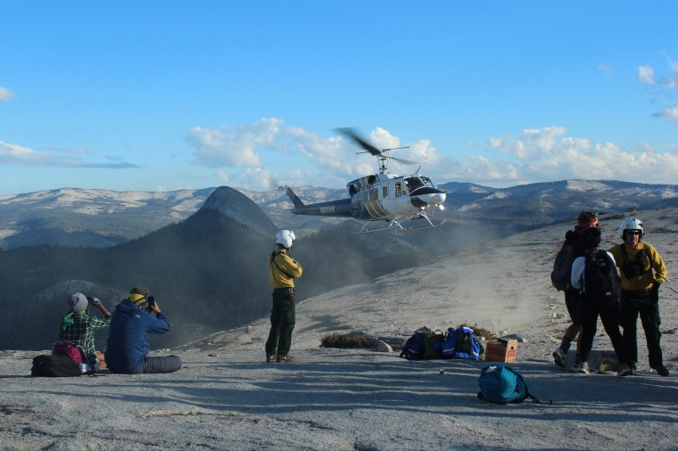 In this Sunday, Sept. 7, 2014 photo provided by Rachel Kirk, hikers are evacuated from Yosemite National Park, Calif. About 100 Yosemite National Park visitors were evacuated from the top of Half Dome by helicopter Sunday when a wildfire that started weeks ago in the park's backcountry grew unexpectedly to at least 700 acres, officials said. (AP Photo/Rachel Kirk)