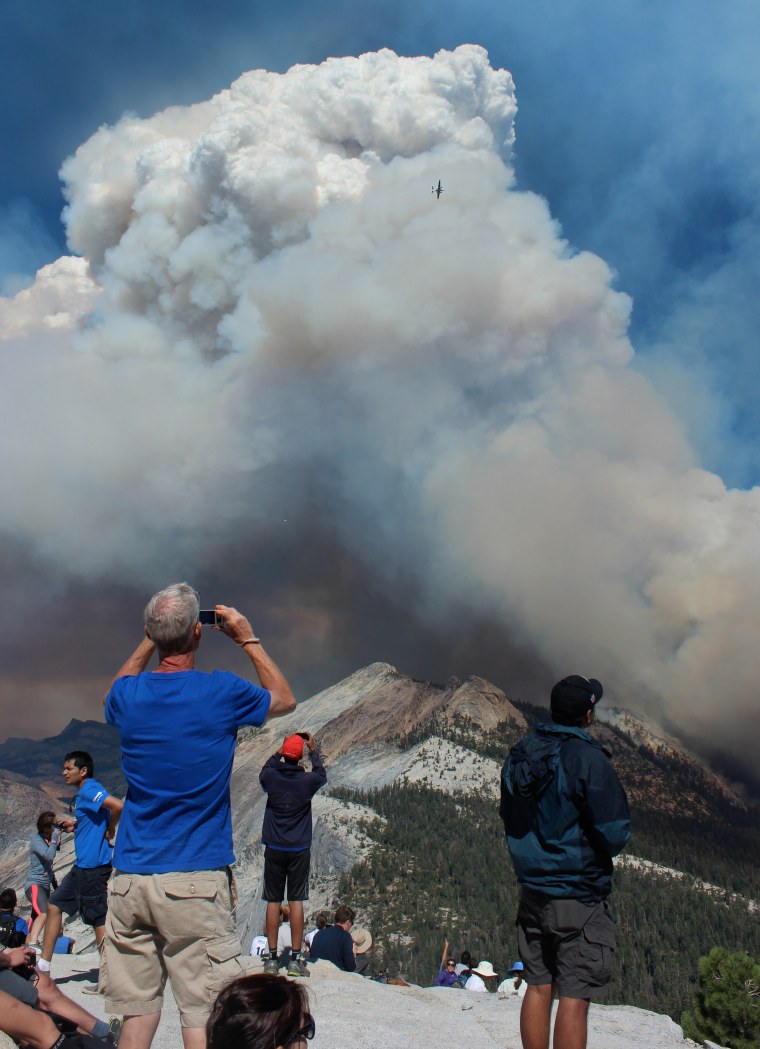 In this Sunday, Sept. 7, 2014 photo provided by Rachel Kirk, hikers take photos of smoke from a fire rising above Little Yosemite Valley near Yosemite National Park, Calif. About 100 Yosemite National Park visitors were evacuated from the top of Half Dome by helicopter Sunday when a wildfire that started weeks ago in the park's backcountry grew unexpectedly to at least 700 acres, officials said. (AP Photo/Rachel Kirk)