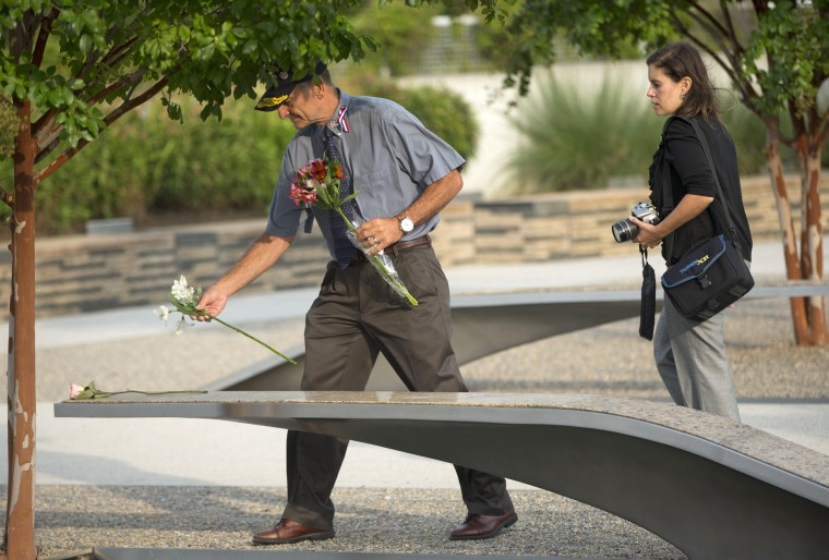 Image: A man places a flower on one of the benches of the Pentagon Memorial in Washington.