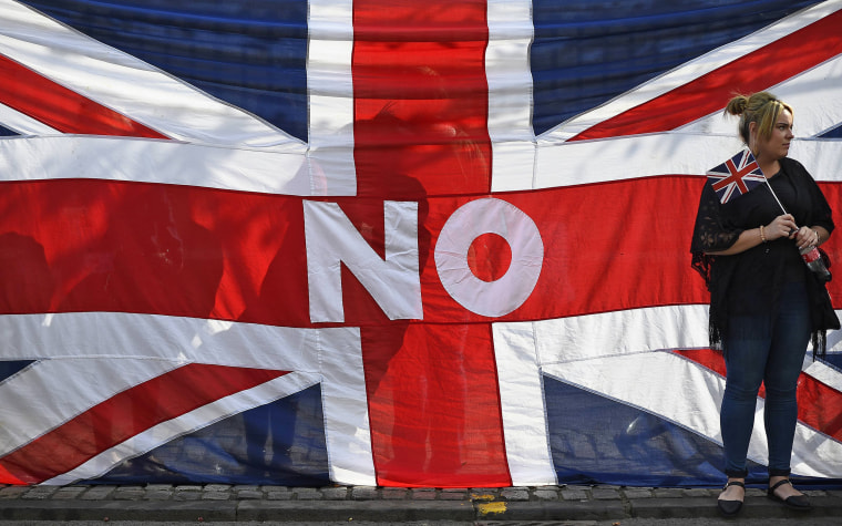 Image: A woman stands by a Union flag as she watches a pro-Union rally in Edinburgh, Scotland