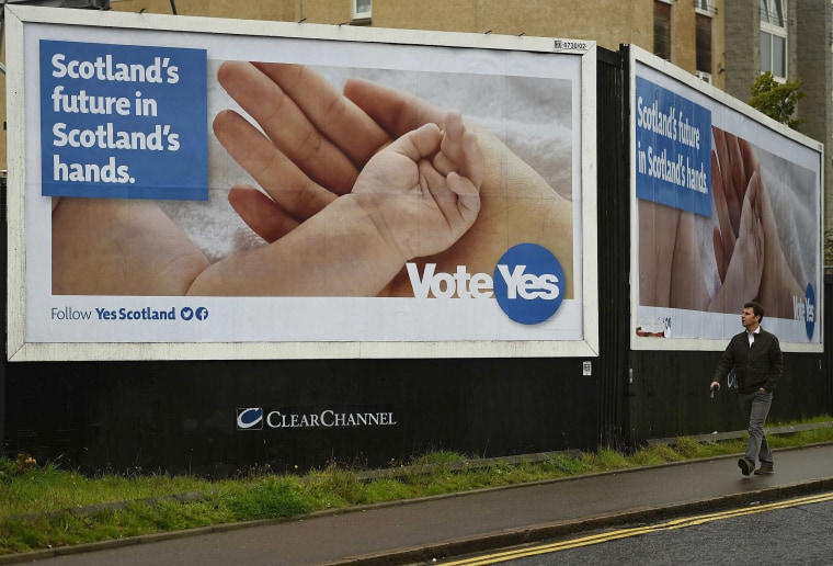 Image: A man walks past a pro-independence poster by the seaside in Aberdeen