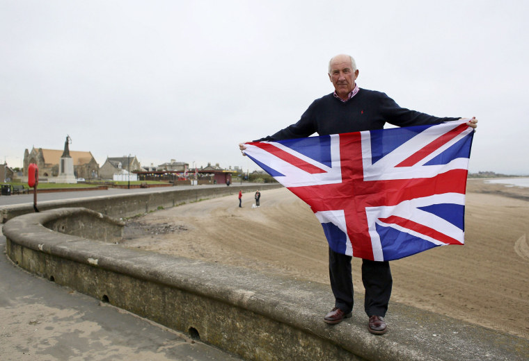 "Image: ""No"" voter Ken Brown, a retired chemical plant manager, poses for a photograph with a Union flag on the beach at Troon, Ayrshire"