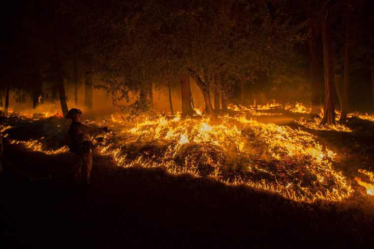 Image: A firefighter battling the King Fire sprays water on a backfire in Fresh Pond, California