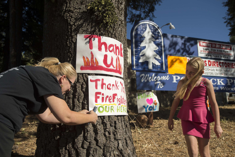 """Image: A woman displays a """"thank you"""" sign for firefighters battling the King Fire in Pollock Pines, California"""