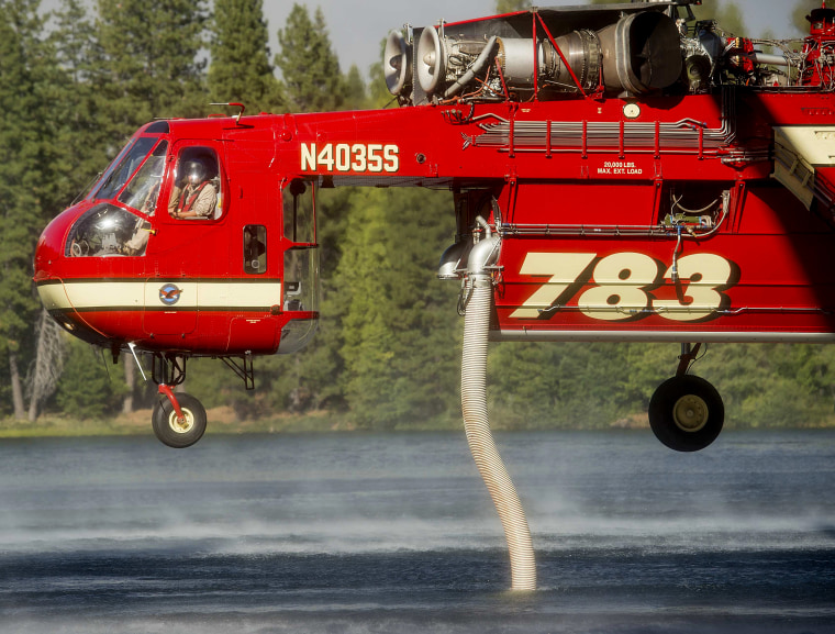 Image: A helicopter draws water from a lake while battling the King Fire in Pollock Pines, California