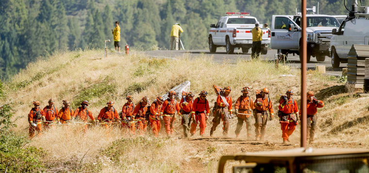 Image: Inmate firefighters return to their truck after battling the King Fire near Fresh Pond