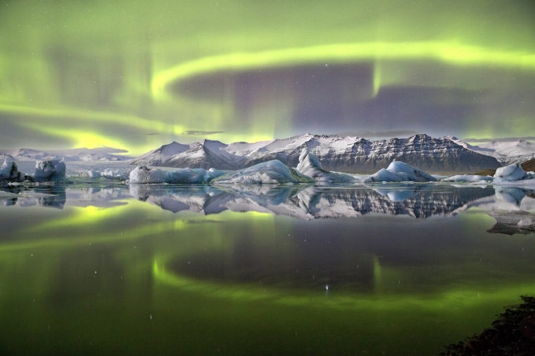 A vivid green overheaded aurrora pictured in Iceland's Vatnajokull National Park reflected almost symetrically in Jokulsrlon Glacier lagoon. A complete lack of wind and currrent combin in this sheltred lagoon scene to crete an arresting mirror effect giving the image a sensation of utter stillness. Despite theis there is motion on a suprising scale, as the loops and arcs of the aurora are shaped by the shifting forces of the Earth's magnetic field.