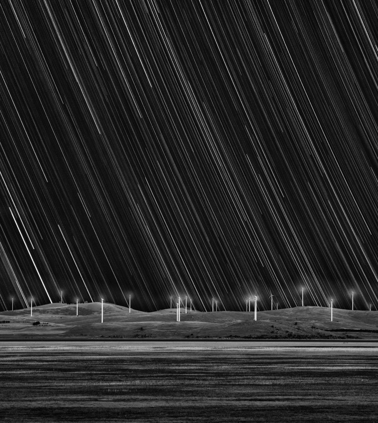 Taken in Australia near the town of Bungendore, this image captures the Capital Wind Farm on the shore of Lake George. The striking monochromatic compostion depicts the power of the wind along with the motion of the sky, illuminated by the shower of stars transforming into trails as the Earth rotates.