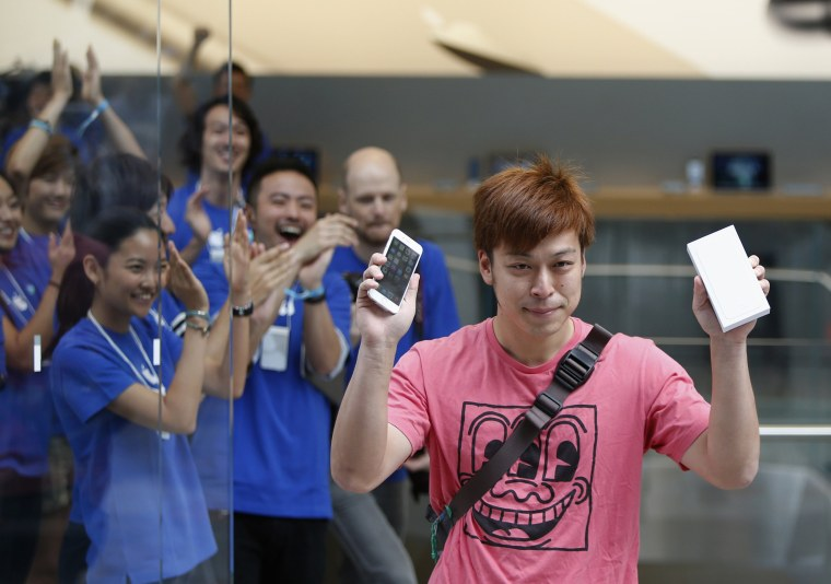 Image: A man shows his iPhone 6 as he walks out from the Apple Store at Tokyo's Omotesando shopping district