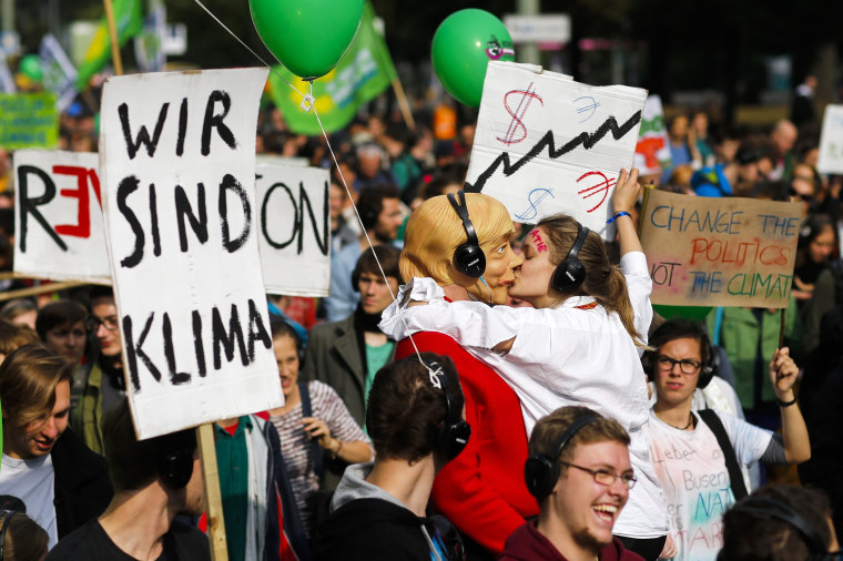 Image: People hold banners and dance during a Climate Change March demanding politicians take tougher action to protect the climate in Berlin