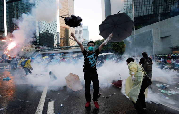 Image: A protester raises his umbrellas in front of tear gas which was fired by riot police to disperse protesters blocking the main street to the financial Central district outside the government headquarters in Hong Kong