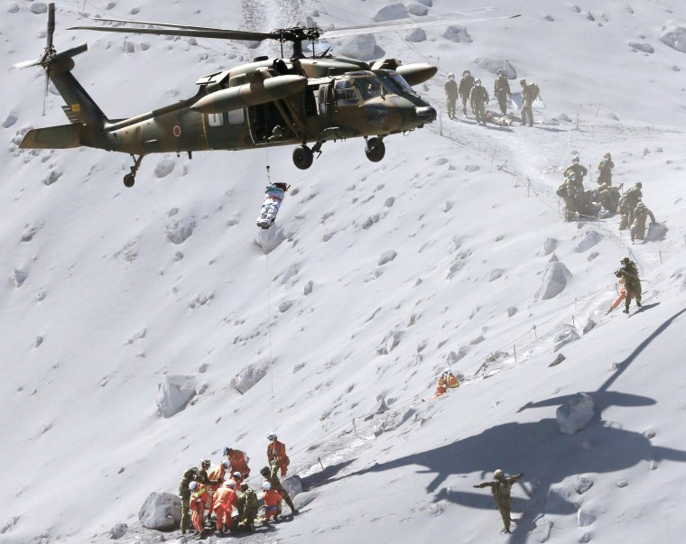 Image: Hiker is lifted by a rescue helicopter of JSDF during a rescue operation at Mt. Ontake, which straddles Nagano and Gifu prefectures, central Japan