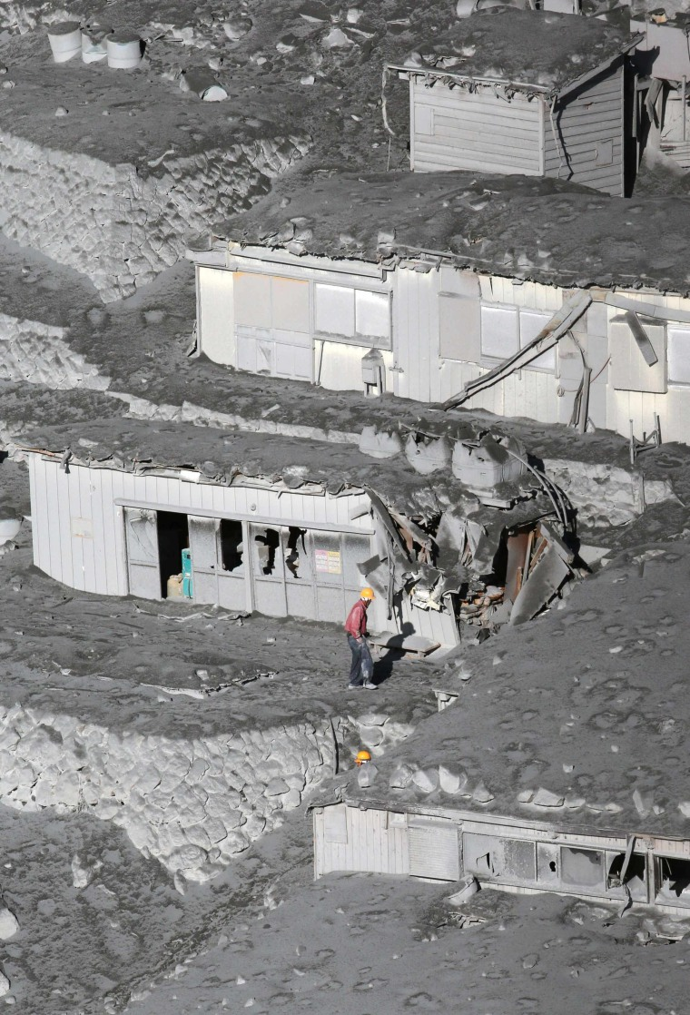 Image: Men walk next to mountain lodges covered with volcanic ash near a crater of Mt. Ontake, which straddles Nagano and Gifu prefectures