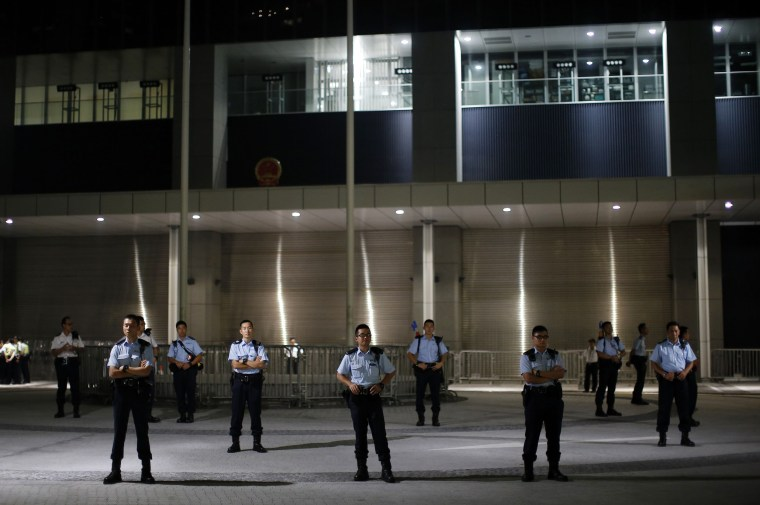 Image: Police officers guard the entrance of the government headquarters building as protesters block the nearby areas in Hong Kong