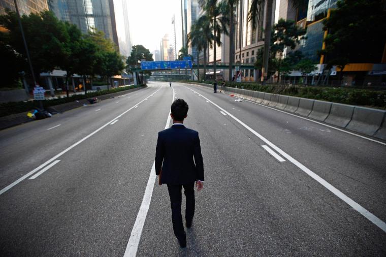 Image: A man walks along an empty street near the central financial district in Hong Kong