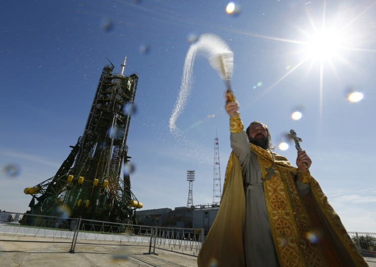 Image: An Orthodox priest conducts a blessing in front of the Soyuz TMA-14M spacecraft set on the launch pad at Baikonur cosmodrome