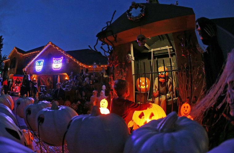 Image: A visitor to a house covered in Halloween decorations looks over the scene in the front yard in the Chicago suburb of Naperville