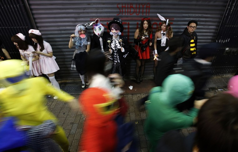 Image: Participants, wearing make-up and costumes, eat candy during Halloween night in Tokyo's Shibuya district