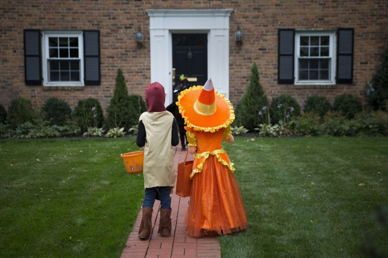 Image: Kids dressed in costumes wait for candy while trick or treating during Halloween in Port Washington, New York
