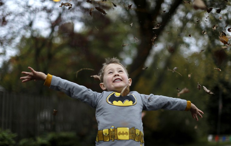 Image: Rocamp, who dressed as Batman, celebrates Halloween at the Flint family's annual Halloween block party in Silver Spring, Maryland