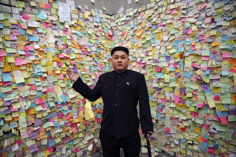 Image: Howard, a 35-year-old Australian Chinese musician and lookalike of North Korean leader Kim Jong Un, gestures in front of a wall with messages of support to pro-democracy protesters in part of Hong Kong's financial central district they are occupyin