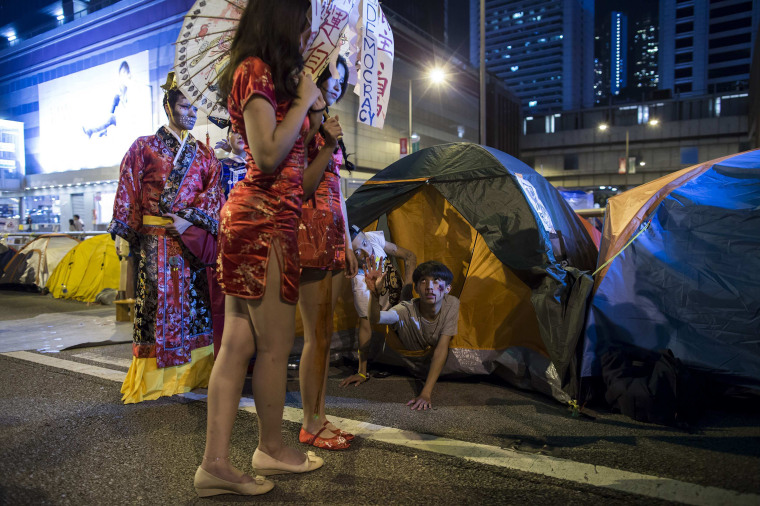 Image: Pro-democracy protesters wearing costumes pose for a photo during Halloween, on a main road which they have blocked, at Admiralty district in Hong Kong