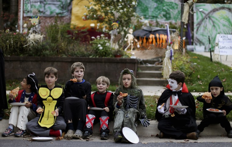 Image: Children dressed in costumes eat pizza at the Flint family's annual Halloween block party in Silver Spring, Maryland