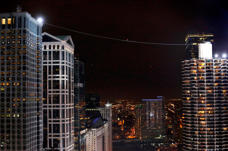 Image: Daredevil Nik Wallenda walks along a tightrope between two skyscrapers suspended 500 feet  (152.4 meters) above the Chicago River
